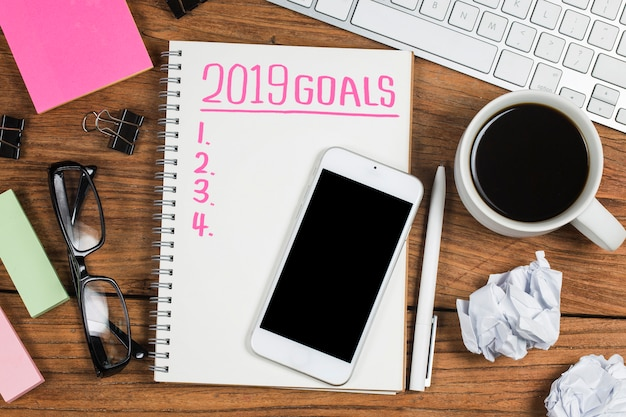 2019 anno nuovo obiettivo, piano, testo di azione sul blocco note con accessori per ufficio. Foto Premium