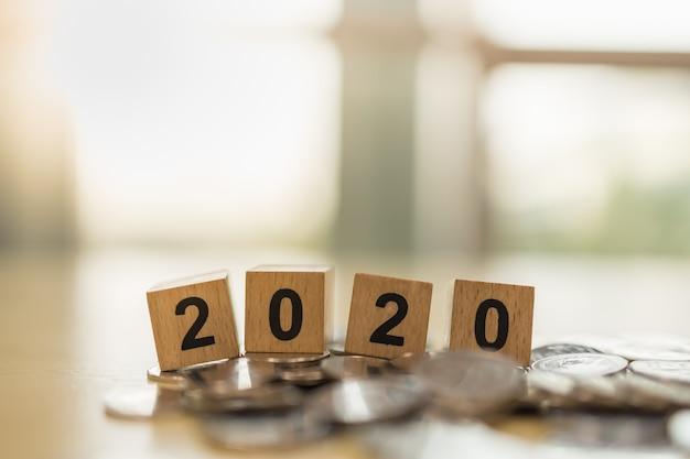 2020 anno nuovo, affari, concetto di risparmio e pianificazione. chiuda in su del giocattolo di legno del blocchetto di numero sul mucchio delle monete con lo spazio della copia Foto Premium