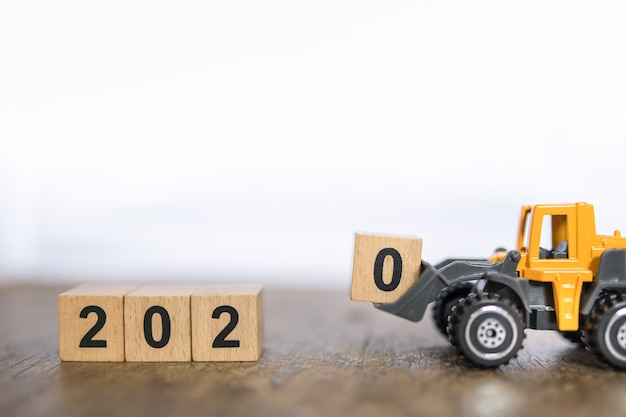 2020 anno nuovo concetto. chiuda su del giocattolo del blocco di legno caricato numero 0 caricato auto della macchina del camion del caricatore del giocattolo sulla tavola di legno e copi lo spazio Foto Premium