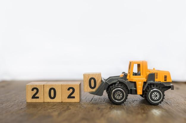 2020 anno nuovo concetto. chiuda su del giocattolo del blocco di legno caricato numero 0 caricato auto della macchina del camion del caricatore del giocattolo sulla tavola di legno e sul fondo bianco con lo spazio della copia Foto Premium