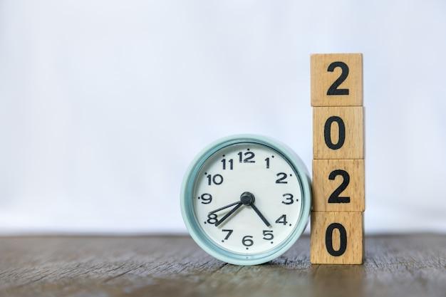 2020 anno nuovo e tempo. chiuda su dell'orologio rotondo e la pila di blocchetti di numero di legno sulla tavola e sul bianco di legno. Foto Premium