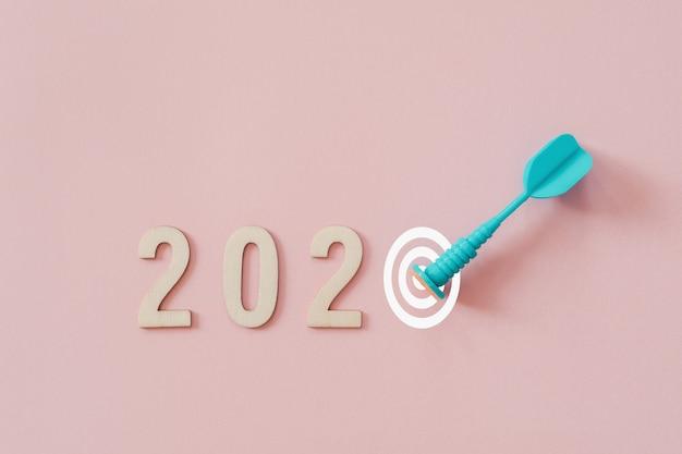 2020 con freccia blu dardo colpire bersaglio su sfondo rosa Foto Premium