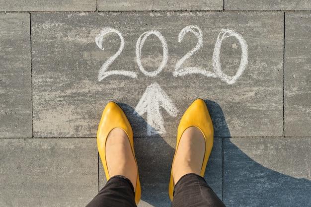 2020 freccia in avanti, scritta sul marciapiede grigio con gambe di donna, vista dall'alto Foto Premium