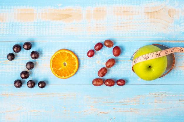 2020 happy new year e new you con frutti sfondi rossi Foto Premium