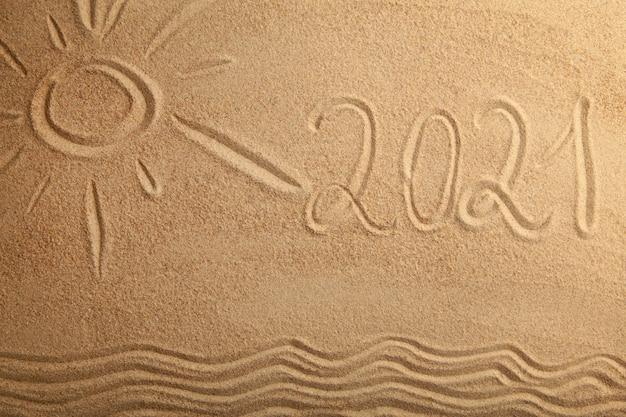 2021 anno nuovo testo con sole su sfondo di sabbia Foto Premium
