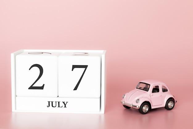 27 luglio, giorno 27 del mese, cubo calendario su sfondo rosa moderno con auto Foto Premium