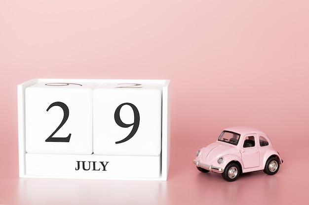 29 luglio, giorno 29 del mese, cubo calendario su sfondo rosa moderno con auto Foto Premium
