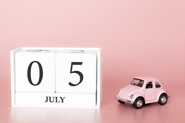 5 luglio, giorno 5 del mese, cubo del calendario su sfondo rosa moderno con auto Foto Premium