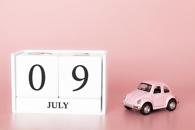 9 luglio, giorno 9 del mese, cubo calendario su sfondo rosa moderno con auto Foto Premium