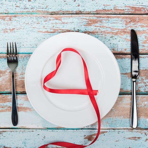 A forma di cuore dal nastro rosso sul piatto con posate Foto Gratuite