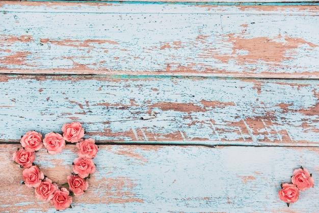 A forma di cuore fatto da boccioli di rose sul tavolo Foto Gratuite