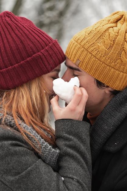 A forma di cuore fatto da neve e coppia Foto Gratuite