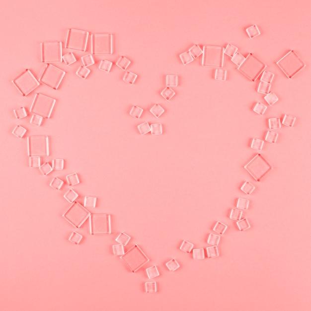 A forma di cuore realizzato con diversi tipi di cubi trasparenti su sfondo corallo Foto Gratuite