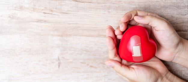 A forma di cuore rosso su fondo in legno. concetto di assistenza sanitaria e giornata mondiale del cuore Foto Premium
