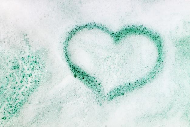 A forma di cuore su sfondo di schiuma di sapone Foto Premium