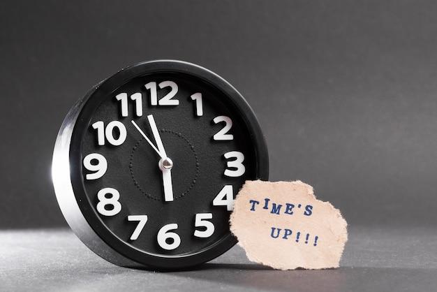 A volte il testo blu su carta strappata vicino all'orologio nero su sfondo nero Foto Gratuite