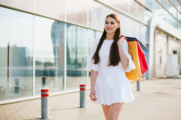 Abbastanza castana con capelli lunghi che camminano con i sacchetti della spesa prima di un edificio moderno Foto Gratuite