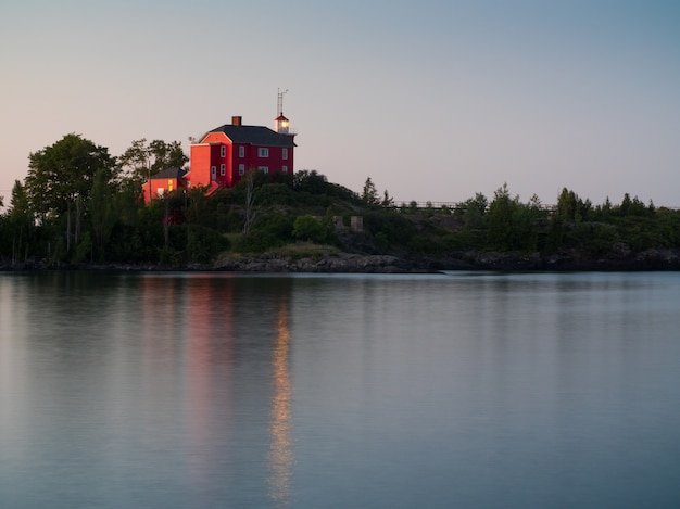 Abbellisca il colpo di un lago calmo con una casa rossa sulla riva Foto Gratuite