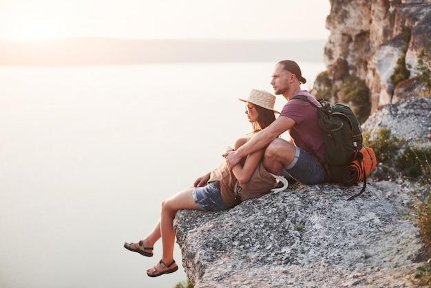 Abbracciando le coppie con lo zaino che si siede in cima alla montagna della roccia che gode della vista costeggia un fiume o un lago. Foto Gratuite