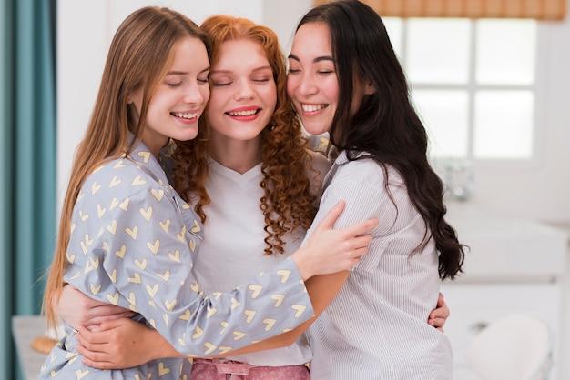 Abbracciare amiche di smiley di vista frontale Foto Gratuite