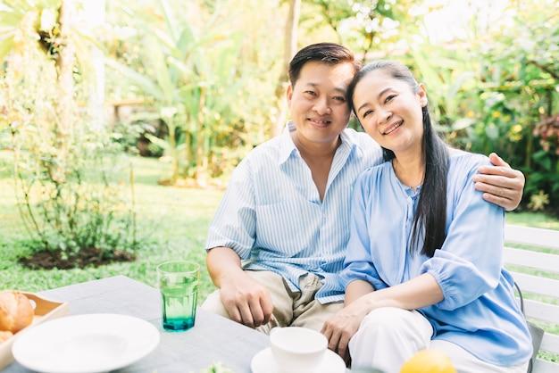 Abbracciare asiatico delle coppie all'aperto in giardino Foto Premium