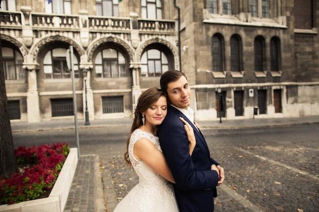 Abbracciare dello sposo e della sposa nella vecchia via della città. weding coppia innamorata. diserbo a budapest Foto Premium