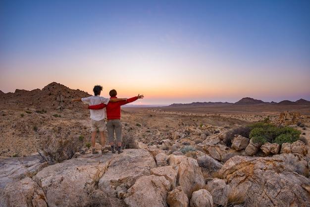 Abbracciare le coppie con le braccia aperte guardando la splendida vista del deserto del namib, maestosa attrazione per i visitatori in namibia. Foto Premium