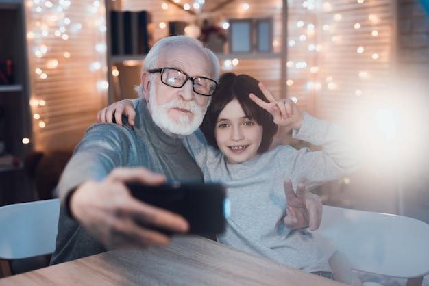 Abbracciare nonno e nipote che fanno selfie Foto Premium