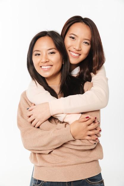 Abbracciare sorridente grazioso asiatico di due sorelle delle signore Foto Gratuite