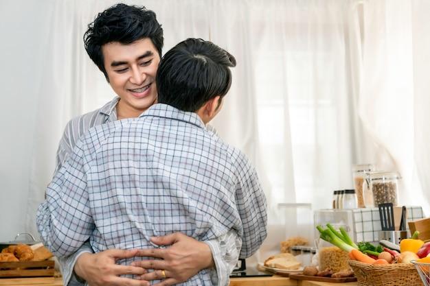 Abbraccio e bacio omosessuali asiatici delle coppie alla cucina di mattina Foto Premium