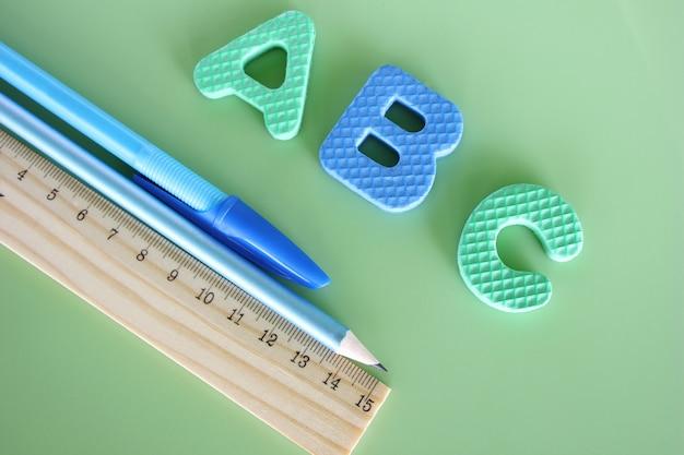 Abc - lettere dell'alfabeto inglese su uno sfondo verde accanto alla penna, matita e righello. Foto Premium
