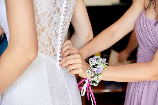 Abito da sposa bianco da portare della sposa. aiutare la sposa a metterla. le damigelle vestono i lacci sul retro Foto Premium