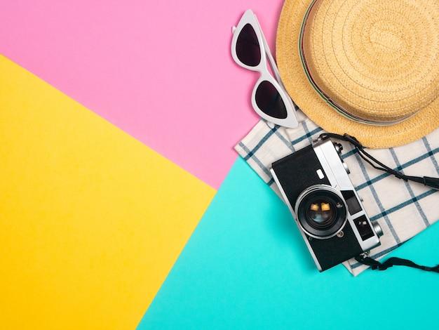 Accessori da spiaggia retro macchina da presa, occhiali da sole, cappello da spiaggia di stelle marine e conchiglia su sfondo blu, rosa, giallo per vacanze estive e vacanze Foto Premium