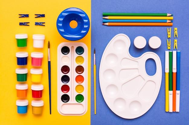 Accessori per disegnare matite, pennarelli, acquerelli, tempere e pennelli su un gialloblu Foto Premium