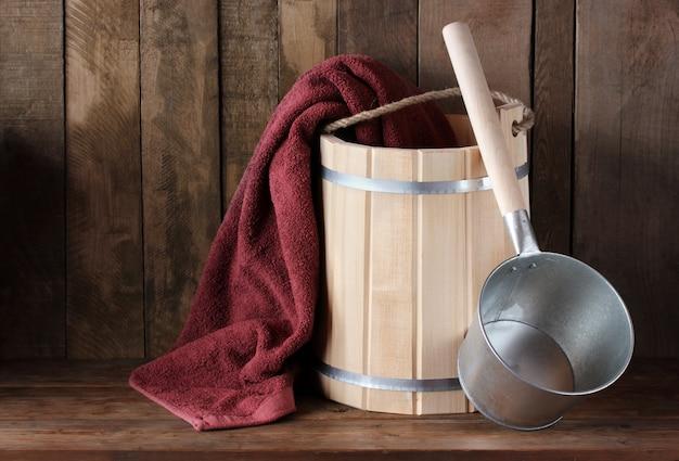 Accessori per il bagno: secchio in legno, asciugamano e secchio di spugna. bagno turco, sauna. Foto Premium