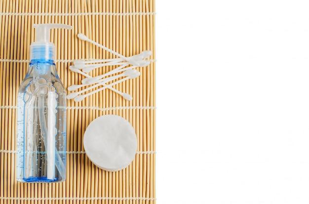 Accessori per struccanti da donna. gel in una bottiglia trasparente, bastoncini di cotone, dischetti di cotone. copia Foto Premium