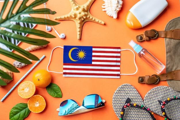 Accessori per vacanze al mare attorno a una maschera protettiva con la bandiera della malesia Foto Premium