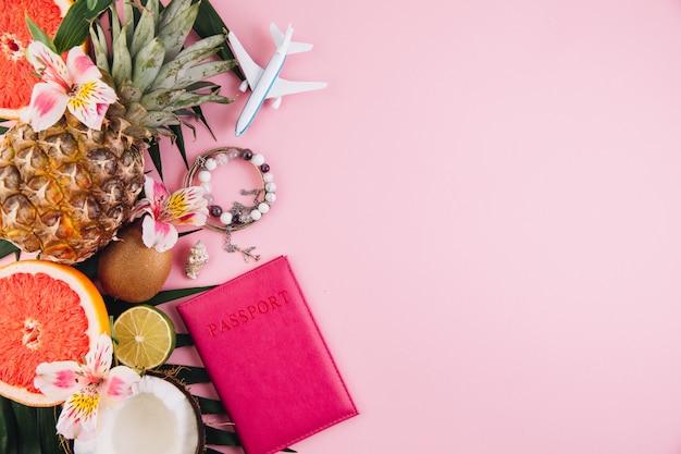 Accessori per viaggiatori e frutti tropicali su sfondo rosa alla moda. colore estivo brillante. Foto Premium