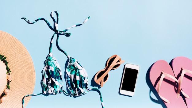 Accessori smartphone e spiaggia su sfondo chiaro Foto Gratuite