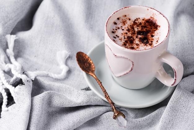 Accogliente colazione invernale mattina a letto scena di natura morta. tazza fumante di caffè caldo o cacao sul plaid di lana. natale . Foto Premium