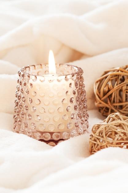 Accogliente concetto di hygge scandinavo con candele accese e decorazioni naturali marroni su soffice coperta bianca. Foto Premium