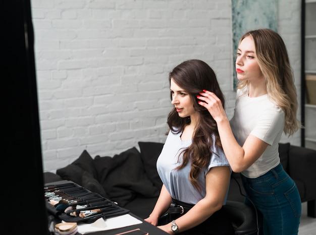 Acconciatura della regolazione del parrucchiere di giovane cliente femminile Foto Gratuite
