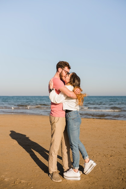 Accoppi l'abbraccio che bacia vicino alla spiaggia alla spiaggia Foto Gratuite