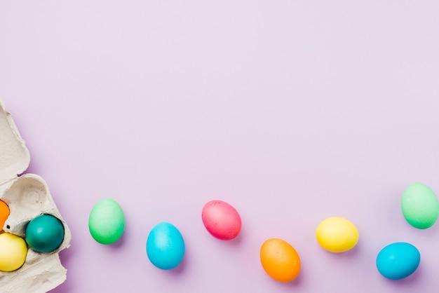 Accumulazione luminosa della fila delle uova colorate vicino al contenitore Foto Gratuite