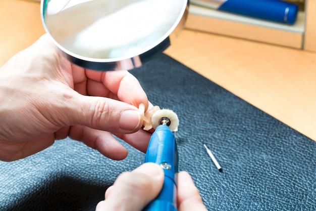 Acoustician che lavora su un apparecchio acustico Foto Premium