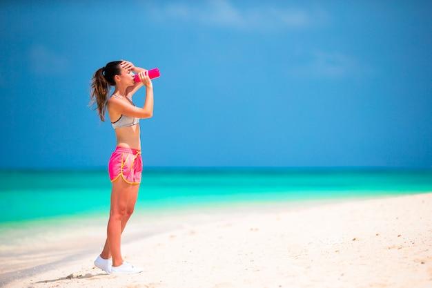 Acqua adatta della bevanda della giovane donna sulla spiaggia bianca Foto Premium