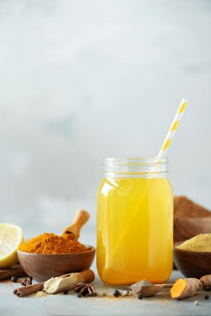 Acqua al limone con zenzero, curcuma, pepe nero. concetto di bevanda calda vegana. ingredienti per la bevanda di curcuma arancione su sfondo grigio cemento Foto Premium