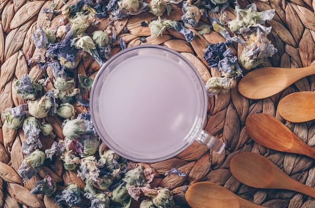 Acqua colorata porpora di vista superiore su fondo trivet con le erbe e i cucchiai del tè orizzontali Foto Gratuite