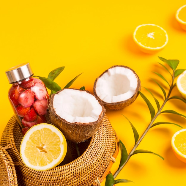 Acqua con fragole, arance, limoni e noci di cocco sul giallo con una borsa di paglia Foto Premium