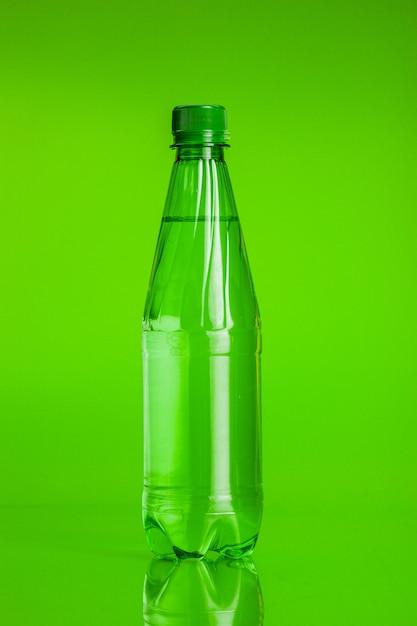 Acqua cristallina in una bottiglia su sfondo verde Foto Premium